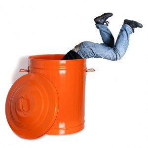 boy dives into a garbage can