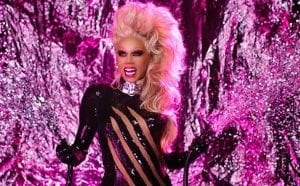 RuPaul holding two live wires apart, She is the potential in the middle