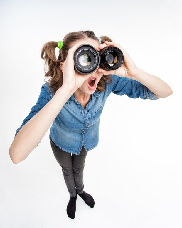 small business growth focus - cute funny girl with two pony tails looking thru photo lenses