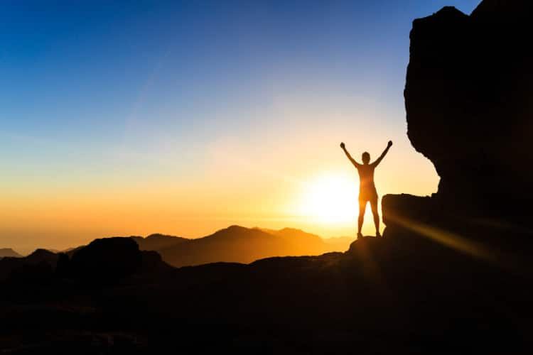 Woman climber success silhouette in mountains