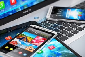 Mobility and modern internet business communication technology concept: macro view of laptop or notebook, tablet computer PC and black glossy touchscreen smartphones with color interfaces with icons and buttons